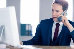 有的商人研究他的计算机和电话 免版税库存照片