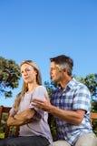 有的夫妇在公园长椅的一个论据 免版税图库摄影