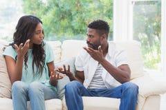 有的夫妇在长沙发的论据 免版税库存图片