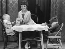 有的女孩与玩偶和熊的茶会 免版税库存图片