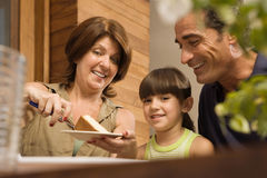 有的女孩和的祖父母蛋糕 免版税库存照片