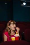 有的女孩玉米花和饮料,当观看电影时 免版税库存照片