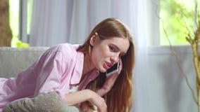 有的女孩说谎在沙发的有趣的电话交谈 股票录像
