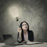 有的女实业家与一个明亮的电灯泡的一个想法 免版税库存图片