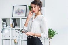 有的女实业家的画象企业电话,谈论细节,计划她的会议使用日志和手机 免版税库存照片