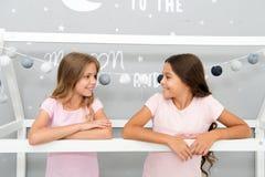 有的好处姐妹 女孩姐妹花费宜人的时间在卧室沟通 令人敬畏的津贴有姐妹 免版税库存照片