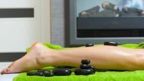 有的妇女与热的石头的腿按摩 免版税库存图片