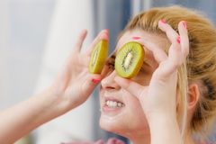 有的妇女在拿着猕猴桃的面孔的胶凝体面具 库存图片