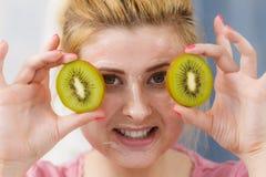 有的妇女在拿着猕猴桃的面孔的胶凝体面具 免版税库存照片