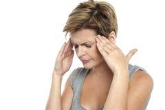 有的妇女头疼。 拿着她的题头 免版税库存图片