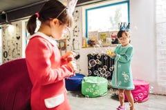有的姐妹唐氏综合症有滑稽的时间在幼儿园 免版税库存照片