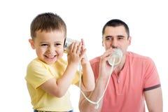 有的孩子和的爸爸与锡罐的一个电话 免版税库存照片