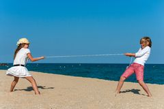 有的孩子在海滩的一场绳索战争。 图库摄影