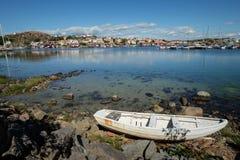 有的小船的湖在另一边的一个小村庄 免版税库存图片