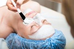 有的少妇躺下在温泉沙龙和一种面部秀丽治疗 面孔的化妆做法 beauvoir 库存图片