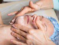 有的少妇躺下在温泉沙龙和一种面部秀丽治疗 面孔的化妆做法 beauvoir 免版税图库摄影