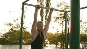 有的帅哥训练在单杠的女子柔软体操户外 在公园做在标志横线的体操特技 影视素材