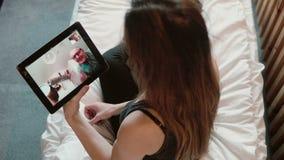 有的年轻女人在片剂的一视频通话 可爱的女孩坐在床和谈话与父亲,电视电话会议 股票视频
