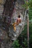有的攀岩运动员休息,当上升,与鞔具和绳索时 abseiling从一个陡峭的岩石的人 免版税库存图片