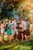 有的朋友与室外饮料的食物和烹调的一个烤肉格栅党 与朋友和人的野营的概念 免版税库存照片