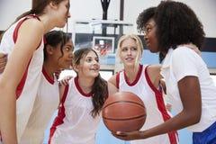有的杂乱的一团的女性高中蓝球运动员与教练的队谈话 免版税库存照片