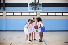 有的杂乱的一团的女性高中蓝球运动员与教练的队谈话 免版税图库摄影