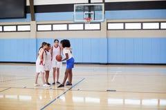 有的杂乱的一团的女性高中蓝球运动员与教练的队谈话 图库摄影