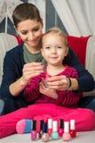 有的母亲和的女儿乐趣绘画指甲盖 免版税库存图片