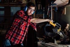 有的深色的人行业木匠建造者锯圆锯一个木板 免版税库存图片