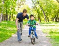 有的父亲和的儿子乐趣周末骑自行车 免版税图库摄影