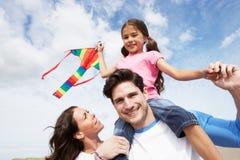 有的父亲和的女儿乐趣海滩假日的飞行风筝 免版税库存图片