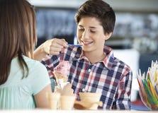 有的男孩草莓冰淇凌,当站立与姐妹时 免版税库存图片