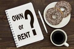 有的笔记本笔记拥有或在办公室桌上的租用咖啡和油炸圈饼 概念购买或租 免版税库存照片