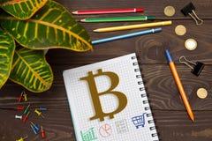 有的笔记本Bitcoin的笔记在办公室桌上的与 免版税库存照片