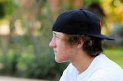 有的粉刺和向后看起来的棒球帽的十几岁的男孩sideway 免版税库存图片