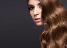 有的美丽的深色的女孩完全卷曲头发和经典构成 秀丽表面 免版税库存照片