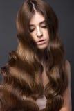 有的美丽的深色的女孩完全卷曲头发和经典构成 秀丽表面 库存照片