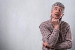 有的老人一张horisontal画象作梦关于某事的严肃的面孔看在旁边握他的手在他的下巴下 Th 库存照片