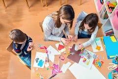 有的老师和的孩子乐趣和创造性的时间一起 免版税库存照片
