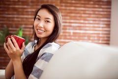 有的长沙发的微笑的亚裔妇女热的饮料 免版税库存照片