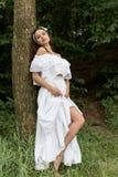 有的黑发的美丽的甜女孩在站立在一棵树附近的白色sundress在森林里在热的夏日 免版税库存图片