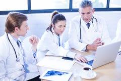 有的医疗队调查膝上型计算机和讨论 库存照片