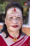 有的画象老妇人在面孔的被着色的斑点在街道 尼泊尔pokhara 免版税库存图片