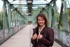 有皮夹克的美丽的深色的妇女在铁桥梁 免版税图库摄影