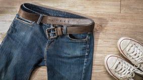 有皮带和肮脏的白色运动鞋鞋子的蓝色牛仔裤在t 免版税库存照片