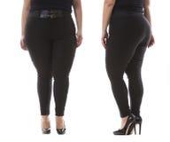 有皮带和高跟鞋的正大小模型穿戴XXL黑女性经典裤子在白色 免版税库存照片