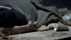 有皮肤烧伤的二赖子盖由毯子睡觉在街道上的在秋天,寒冷 免版税库存照片