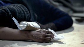 有皮肤烧伤的无家可归者睡觉在肮脏的街道上的,盖从寒冷 库存照片