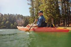 有皮船的成熟人在湖 免版税库存照片