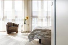 有皮革扶手椅子的卧室 免版税库存图片